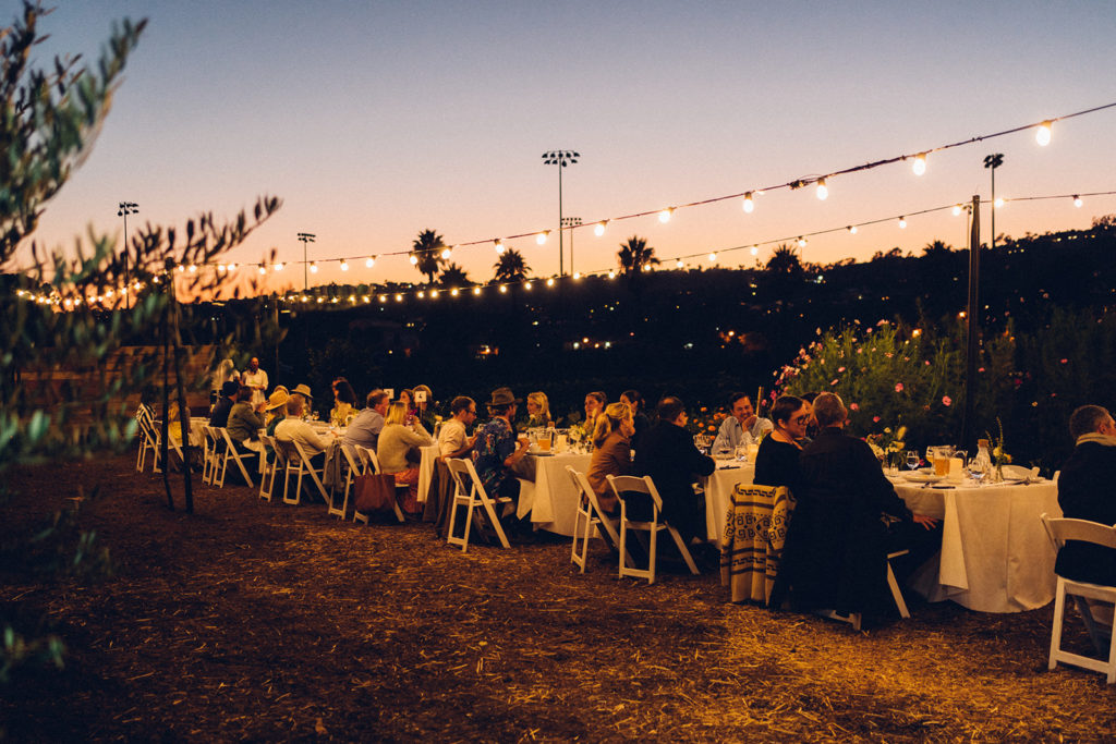 Long row of tables filled with dinner guests and friends in middle of farm field.