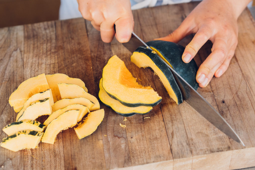 Acorn squash cut in half and then in slices.